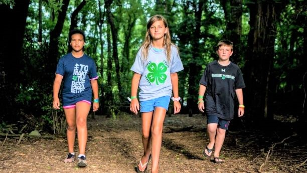 Three 4-H members in the woods